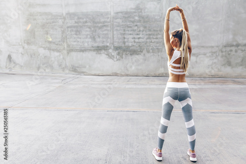 Fitness sport woman in fashion sportswear doing stretching exercise over gray wall © Alena Ozerova