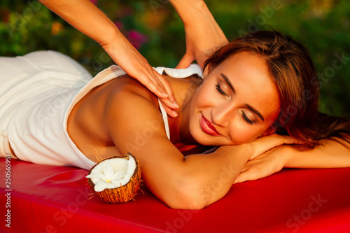 Leinwanddruck Bild Ayurvedic relaxing massage ,health beauty happy closed eyes woman in spa salon getting massage on the holiday beach.Beautiful girl enjoying day spa resort, lying down on the table treatment procedure