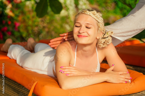 Leinwanddruck Bild Ayurvedic relaxing massage ,health beauty happy blonde woman in spa salon getting massage on the holiday beach.Beautiful girl enjoying day spa resort, lying down on the table treatment procedure