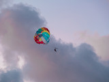 Parasailing in evening. Bright parachute on a background of a sunset