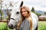 Fototapeta Konie - Beautiful blond woman with pony, looking at camera © sanneberg