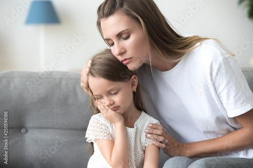 Leinwandbild Motiv Loving mother embracing, comforting upset little daughter close up