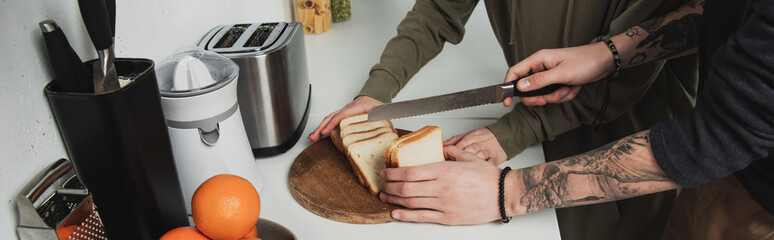 cropped view of couple preparing breakfast and cutting bread in kitchen © LIGHTFIELD STUDIOS