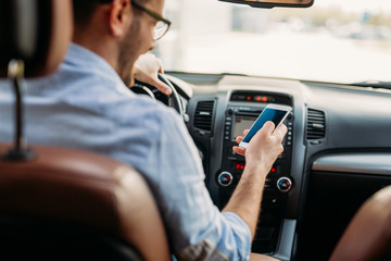 Man looking at mobile phone while driving © nd3000