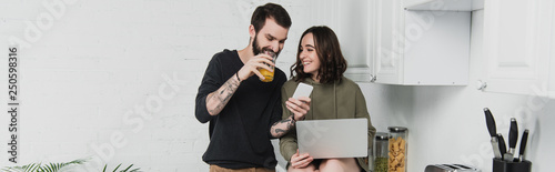 man drinking juice and using smartphone while woman using laptop during breakfast in kitchen