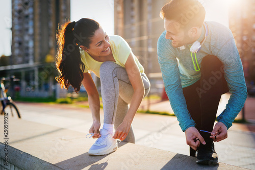 Runners tying running shoes and getting ready to run