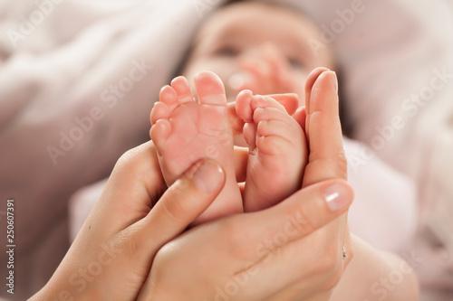 Mother massages her little baby's feet