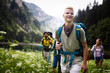 Leinwanddruck Bild - Group of happy friends with backpacks hiking together