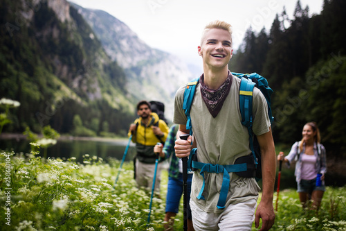 Leinwanddruck Bild Group of happy friends with backpacks hiking together