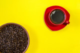 Red mug of freshly brewed coffee with roasted beans in a ceramic clay pan on a yellow background