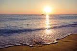 Piaszczysta plaża o zachodzie słońca