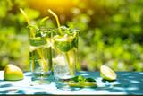 Two glasses of homemade lemonade under bright sun - 250618340