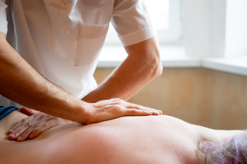 Masseur doing massage of back young girl.