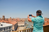 Tourist man travel in Italy, Venice. View on Grand canal. Man making photo using his smartphone standing and looking on roof top. Man tourist travel in Italy. Copyspace