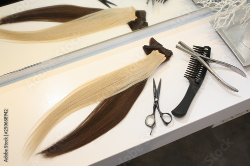 different extensions with comb and scissors in hair salon