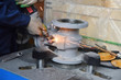 Quadro The base for the valve is mounted on an iron table for assembly at the factory and the worker, using a grinding tool, grinds a gray body, sparks fly