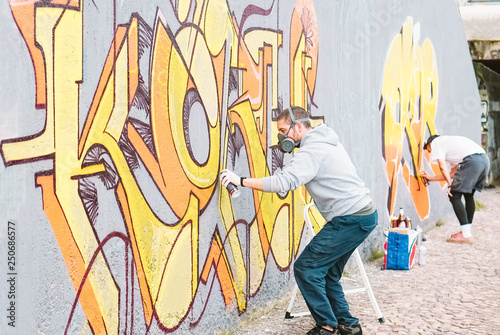 Graffiti artists painting colorful mural on a grey wall - Creative men performing drawing murals - Concept of street and modern art, culture and youth lifestyle - 250686577