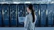 Back Shot of a Female Data Center IT Specialist Works on Laptop Computer Next to Server Rack Corridor. Running Diagnostics or Doing Maintenance Work.