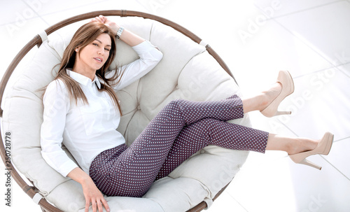 Leinwanddruck Bild tired young woman resting in a soft round chair