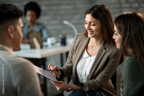 Happy insurance agent analyzing investment plans with her clients.
