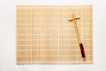 Empty Asian Food Background. Bamboo mat and chopsticks on white background © colnihko