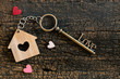 Leinwanddruck Bild - House key in heart shape with home keyring on old wood background decorated with mini heart