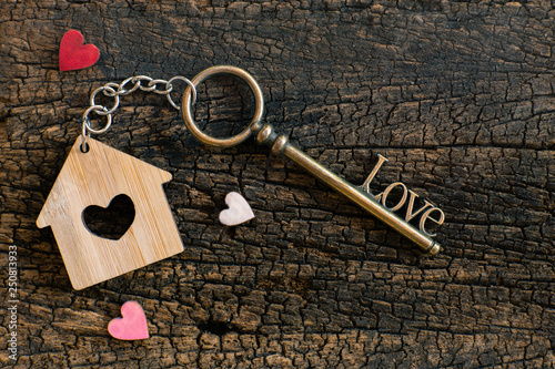 Leinwanddruck Bild House key in heart shape with home keyring on old wood background decorated with mini heart