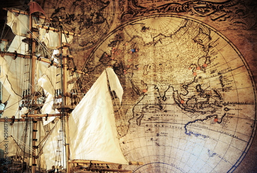 Old pirate sailboat, ship model,cannons,world map.Travel and marine engraving background. Retro style.Treasure hood concept. © erkipauk