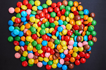 Color small chocolate dragee. Candy on a black background.