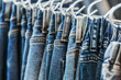 many models of jeans from different denim, texture, color hang on hangers