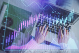 Hands typing on laptop. Business and Financial concept. Double exposure of stock market charts. - 250865561