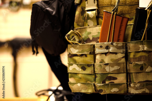 Soldier with camouflage bulletproof vest and Machine gun. Close up. mock up. Toned sepia © skvalval