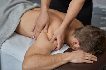 Young handsome man enjoying a back massage. Professional massage therapist is treating a male patient in apartment. Relaxation, beauty, body and face treatment concept. Home massage. © YURII MASLAK