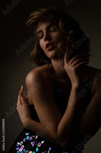 Seductive brunette model with curly hair wears sparkling dress posing with contrast light at studio