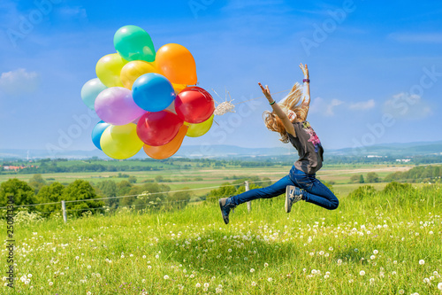 Leinwandbild Motiv Glückliches Mädchen spring mit bunten Luftballons über eine grüne Wiese