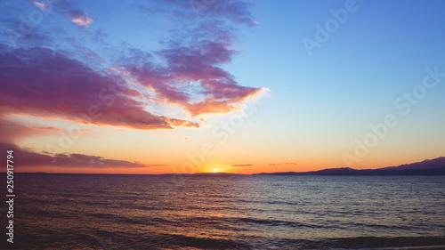 Sunset over seaside, mountains on the horizon