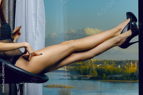 Leinwandbild Motiv Beautiful female legs with black heels  on blurred panoramic background of the city on the river. Girl  sitting on a bar stool. Perfect long female legs. Attractive model posing and caresses his legs