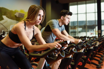 Couple in a cyclo indoor class wearing sportswear.