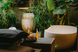 Outdoor spa salon. Massage oils, burning incense sticks with smoke, towels, flowers on wooden  stone table. Bath, green leaves on background - 250959529