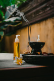 Outdoor spa salon. Massage oils, burning incense sticks with smoke, towels, flowers on wooden  stone table. Bath, green leaves on background - 250959538