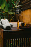 Outdoor spa salon. Massage oils, burning incense sticks with smoke, towels, flowers on wooden  stone table. Bath, green leaves on background - 250959743