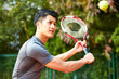 young asian man playing tennis outdoors