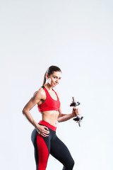 Fit woman with dumbbells in sportswear red-black on a gray background. © BestForYou