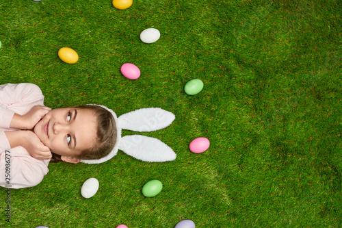 Girl lying on lawn near Easter eggs