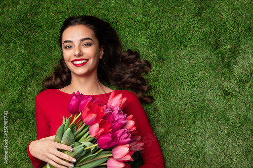 Happy sensual model with pink flowers on meadow  - 250987742