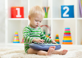 Kid boy plays toy piano sitting on floor in nursery