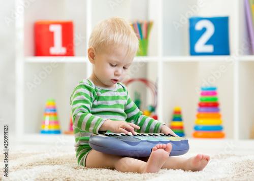 Leinwandbild Motiv Kid boy plays toy piano sitting on floor in nursery