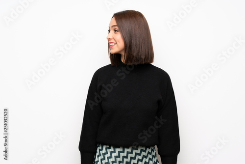 Young woman over white wall looking to the side