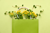 Yellow primrose flowers in a green shopping bag with space for text on yellow paper