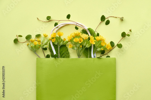 Yellow primrose flowers in a green shopping bag with space for text on yellow paper © tilialucida